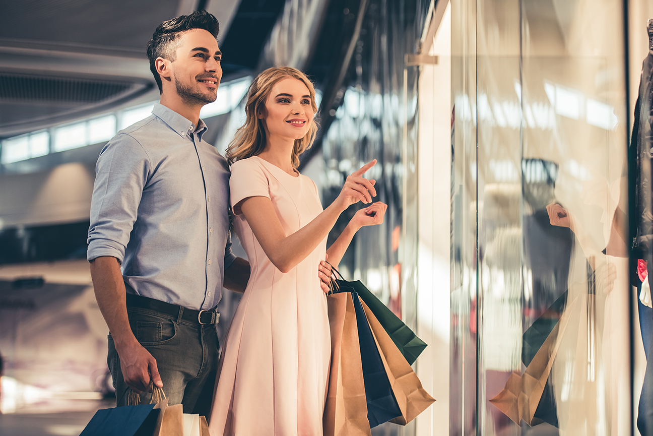 Beautiful couple with shopping bags is talking and smiling while doing shopping in the mall