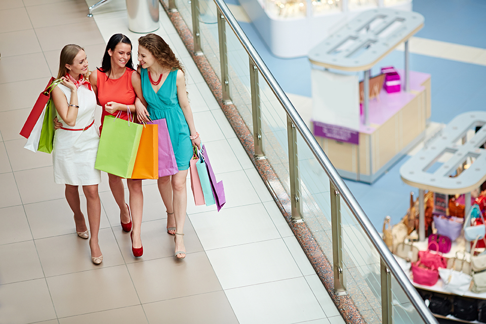 Happy female friends walking along shopping center, carrying shopping bags and talking